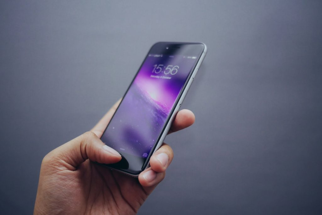 person holding space gray iPhone X phone number porting device