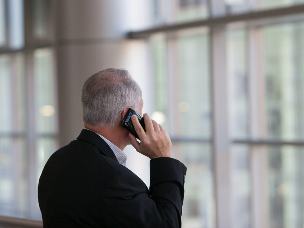 man holding black smartphone in front of a windowpane business phone system