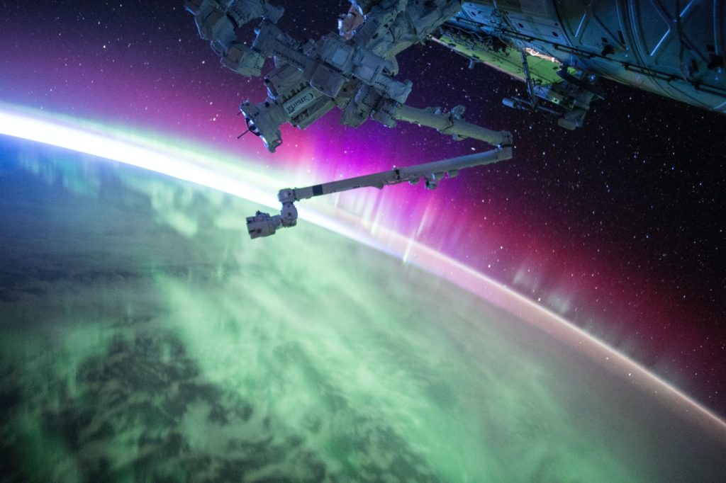 photography of purple and green aurora beam below grey space satellite starlink