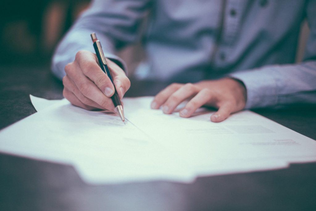 man writing on paper signing service level agreement