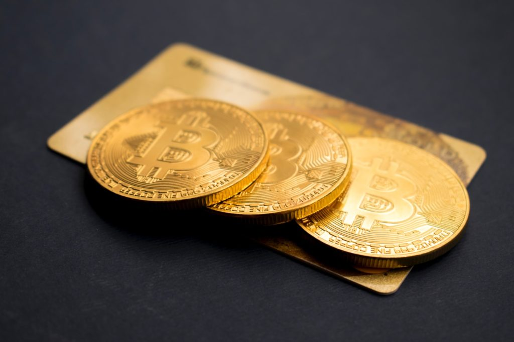 three round gold-colored Bitcoin tokens cryptocurrency and blockchain